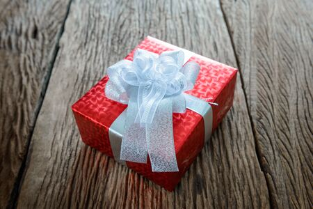 glittery: Packed glittery red present container on vintage wooden board.