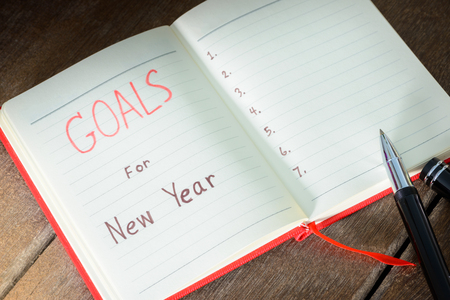 New Years goals with with notebook and pen. New Years goals are resolutions or promises that people make for the New Year to make their upcoming year better in some way
