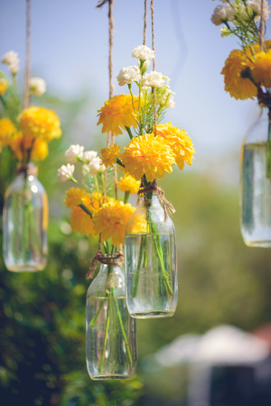 The marigold flowers in a glass bottle hanging. Flower vase arrangements. Vintage tone colour