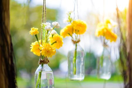 The marigold flowers in a glass bottle hanging. Flower vase arrangements 版權商用圖片