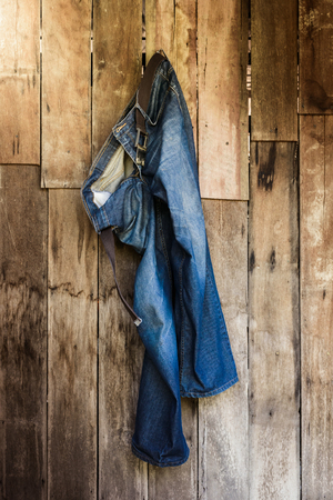 dirty old man: Vintage,Jeans hanging on the wooden wall background