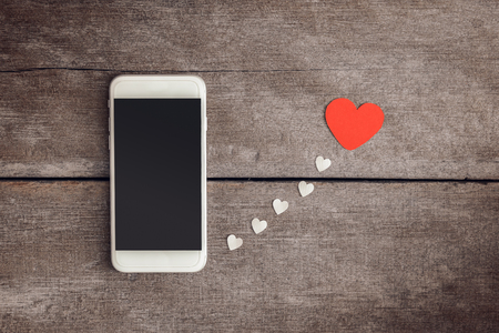 Smartphone and hearts paper on wooden background. valentien or Sending love through social networks Foto de archivo