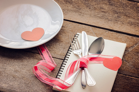 Centrepiece: Valentines day table setting with plate, knife, fork, red ribbon, notebook and hearts on wooden table, Valentines day background
