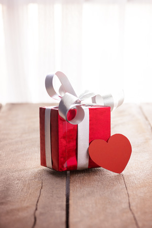 text box: Red gift box and heart (with space for text) on white wooden table. valentine concepts