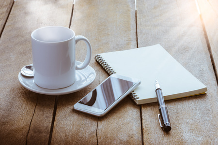 cup of coffee, notebook, pen and smart phone on wooden table