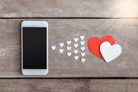 valentine heart: Smartphone and hearts paper on wooden background. valentien or Sending love through social networks Stock Photo