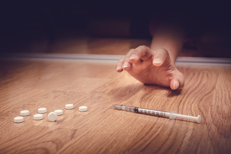 overdose female drug addict hand, drugs narcotic syringe on floor