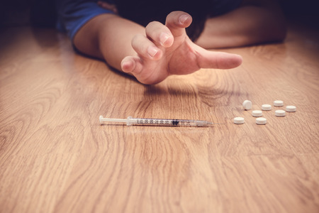 abuso: Sobredosis de la mano masculina adicto a las drogas, jeringuilla drogas estupefacientes en el piso Foto de archivo