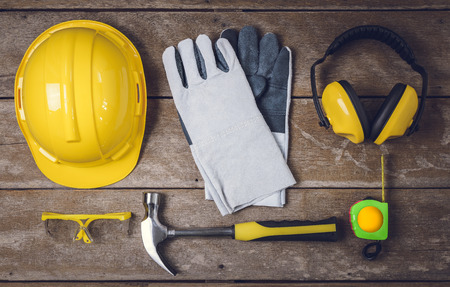 Standard construction safety equipment and Tools on wooden table. top view