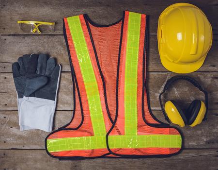accidente trabajo: equipo de seguridad estándar de construcción en la mesa de madera. vista superior
