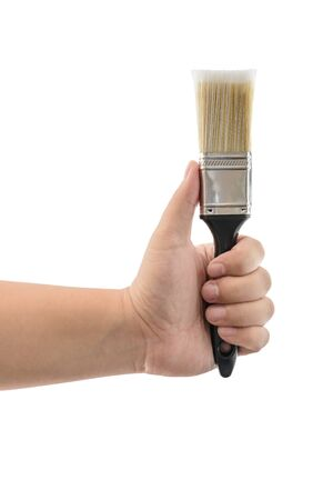 caulk: hand holding paint brush with plastic black handle isolated on a white background Stock Photo