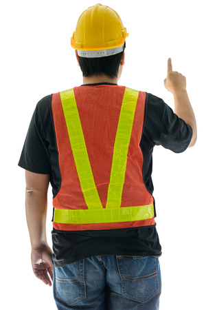 pointy hat: rear view of male construction worker with Standard construction safety equipment and pointed the finger isolated on white background Stock Photo