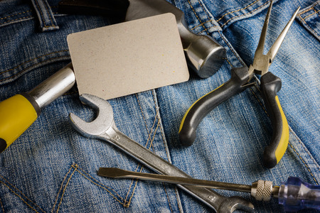 toolset: Several tools on a denim workers pocket and business cards on wooden background Stock Photo