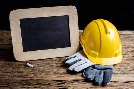 protective clothing: slate board and protective clothing on wooden background