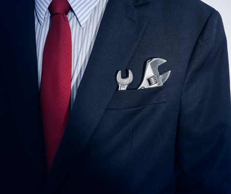 Closeup Businessman with spanner in suit pocket Stock fotó