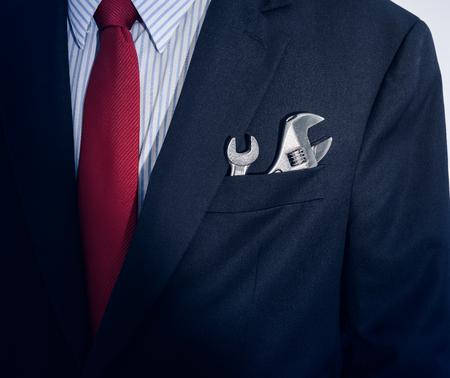 Closeup Businessman with spanner in suit pocket Foto de archivo