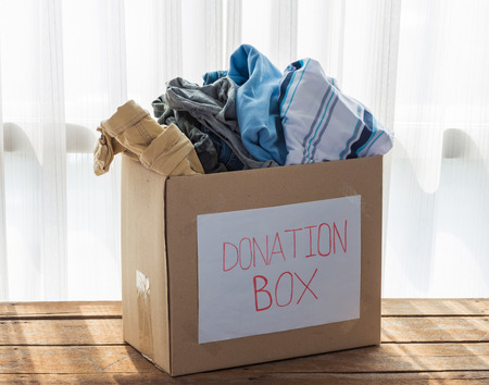open box: Clothing donation box on wooden background