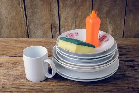 lavar platos: vac�os platos y los taza con l�quido para lavar platos, esponjas de mesa de madera Foto de archivo