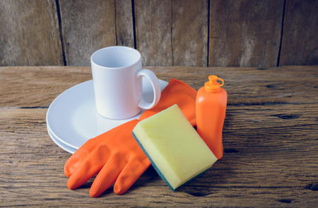 rubber gloves: empty clean plates and cup with dishwashing liquid, sponges, rubber Gloves on wooden table Stock Photo