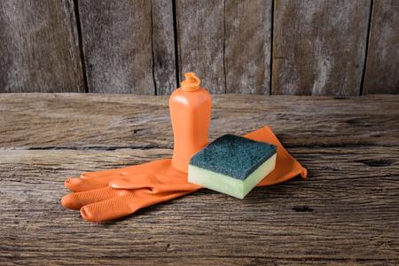 lavar platos: líquido para lavar platos, esponjas, guantes de goma en la mesa de madera