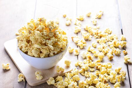 popcorn bowl: White bowl of popcorn on the wooden table, selective focus at popcorn in a bowl Stock Photo