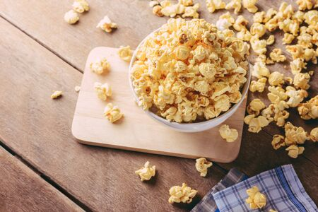 bowls of popcorn: White bowl of popcorn on the wooden table, selective focus at popcorn in a bowl Stock Photo