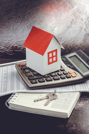 Real estate investment. House, key and calculator on table. Concept home loans Foto de archivo
