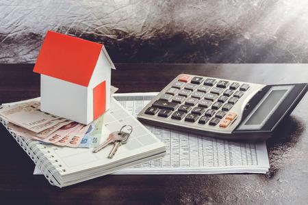 cash money: vivienda unifamiliar en la pila de dinero. Concepto de bienes inmuebles.