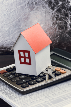 Real estate investment. House, key and calculator on table. Concept home loans Stock Photo