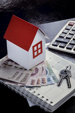 lender: Single family house on pile of money. Concept of real estate.