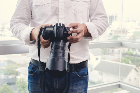camera lens: professional photographer adjusts the camera before shooting, hands, camera, background Stock Photo