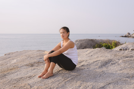 seashores: Young woman sitting at the sea at sunrise. After Exercise