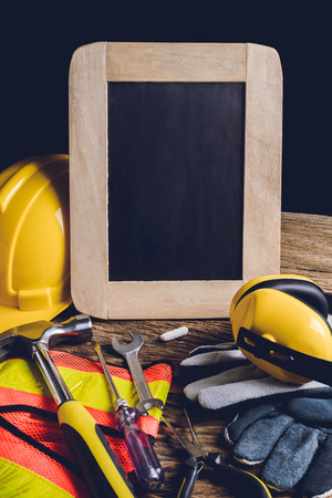 protective clothing: slate board, protective clothing and Hand Tool on wooden background