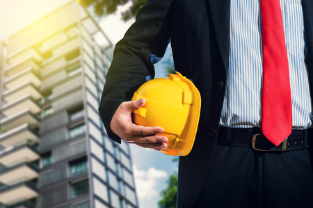Businessman, engineer in suit holding helmet background is building apartment