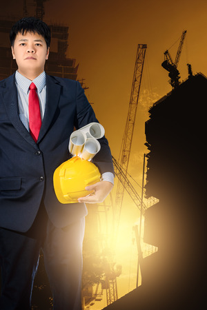indenture: engineer holding yellow helmet for workers security on background of new highrise apartment buildings and construction cranes on background of evening sunset cloudy sky Silhouette Crane lifts load Stock Photo