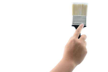 caulk: back view of hand holding paint brush with plastic black handle isolated on a white background with clipping path Stock Photo