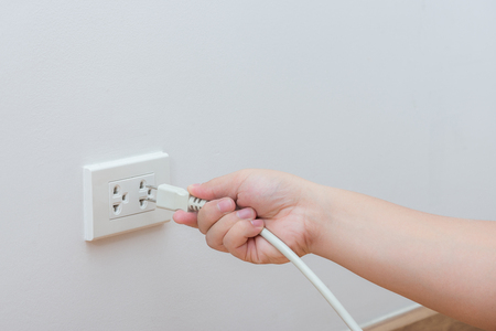 unplugging: Unplug or plugged in concept,hand holding and pull electric plug