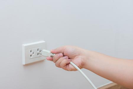 Desconectar o enchufado concepto, explotación de la mano y tirar del enchufe de corriente