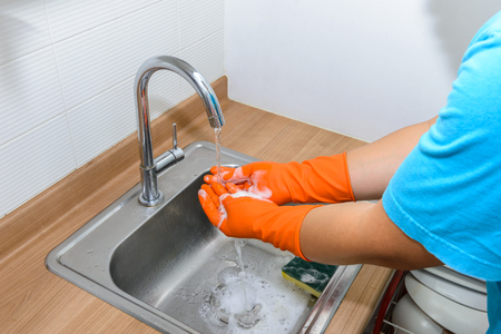 Hygiene. Cleaning Hands wearing gloves. Washing hands in the kitchen Stock Photo