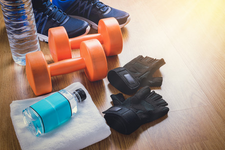 protective gloves: Fitness equipment. Sneakers, water, protective gloves on wooden background Stock Photo