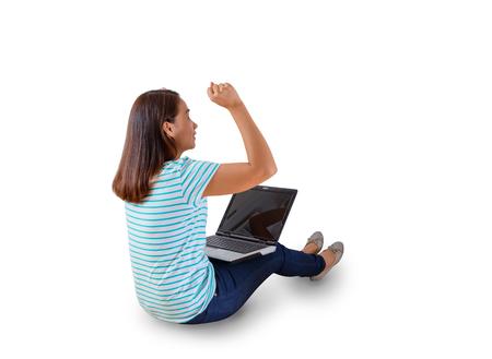 puños cerrados: Vista posterior de la mujer que se sienta en el suelo blanco con un ordenador portátil levantando los brazos con una mirada de los conceptos de éxito. aislado en el fondo blanco