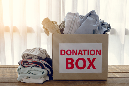 Clothing donation box on wooden background