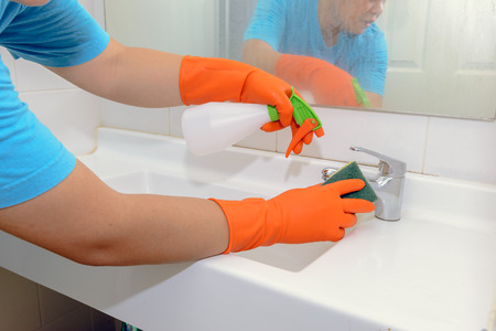 doing chores: man doing chores in bathroom at home, cleaning sink and faucet with spray detergent. Cropped view Stock Photo