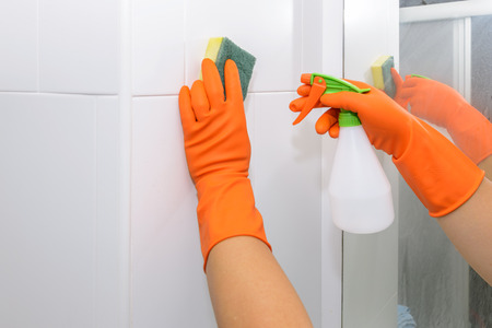man doing chores in bathroom at home, cleaning wall with spray detergent. Cropped view Stock Photo