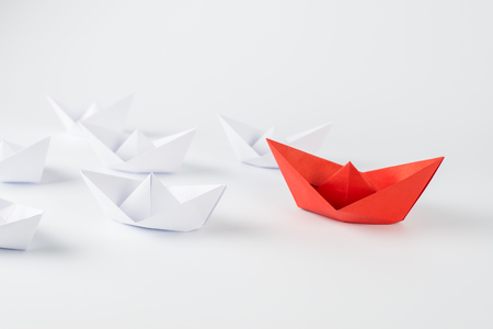Leadership concept with red paper ship leading among white Stock Photo