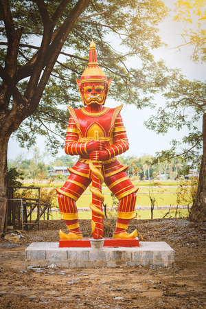 Red Giant Statue standing and hold baton
