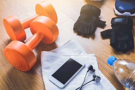 protective gloves: Fitness equipment. Sneakers, water,smartphone, protective gloves on wooden background