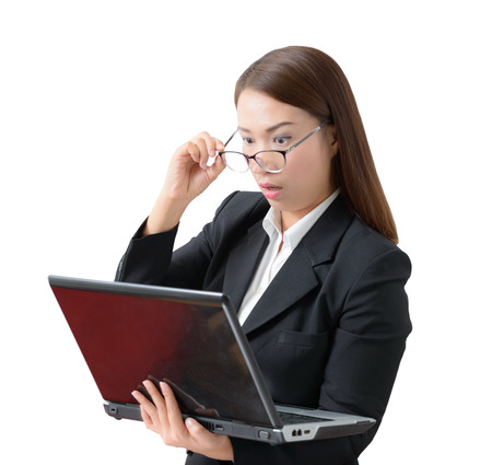 Frightened and stressed young business woman  Hand holding glasses and open mouth her Eye staring to  laptop. on white background. surprised concept Stock Photo