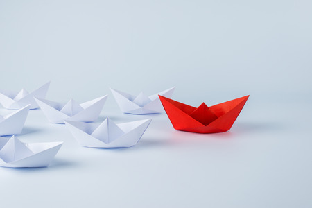 Leadership concept with red paper ship leading among white Stock fotó