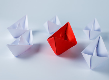 supervisión: Leadership concept with red paper ship leading among white Foto de archivo